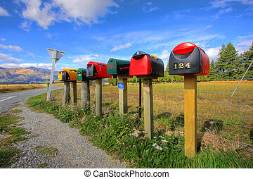 Colorful row of post boxes by a roadside