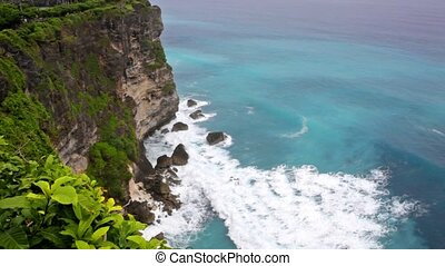 Waves of the Indian Ocean break about coastal rocks Bali...