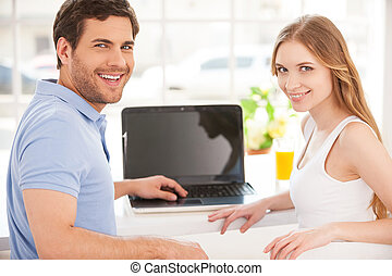 Surfing the net together. Handsome young man sitting at the...