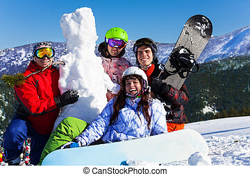Four young people with snowboard and snowman - Four positive...
