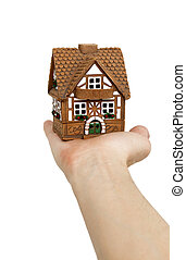 Miniature model of a house on a hand (isolated from...