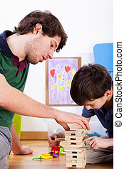 Playing with boys' toys - Son and dad playing building a...