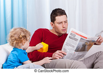 Bored child looking at father reading newspaper