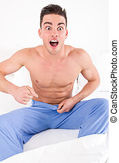 handsome half naked man having problems with genitals and...