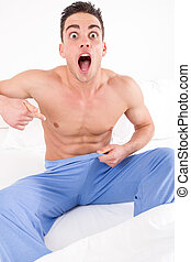 upset man on bed in pajamas having problems with impotence -...