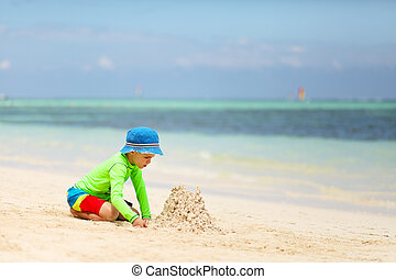 Caucasian boy building sand castle on tropical beach