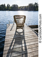 Rocking chair on small lake dock - Wicker rocking chair on...