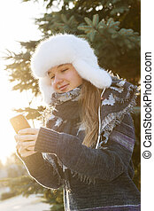Young girl with cell phone in winter - Portrait of teenage...