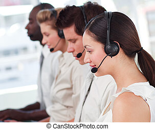 Mixed race business called centre with people on headsets