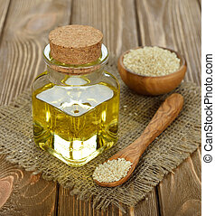 sesame oil in a glass bottle on a brown background
