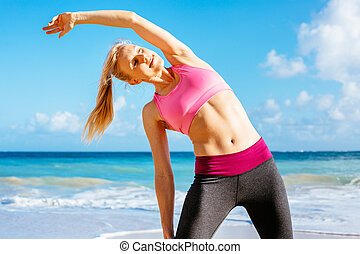 Athletic Fitness Woman Stretching At the Beach, - Athletic...