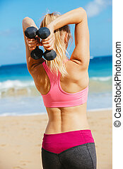 Fitness woman with barbells working out. Exercising outdoors...