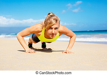 Attractive woman doing push ups outside.