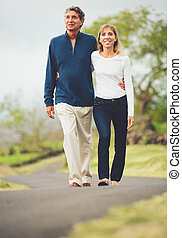 Happy loving middle aged couple walking on beautiful country...