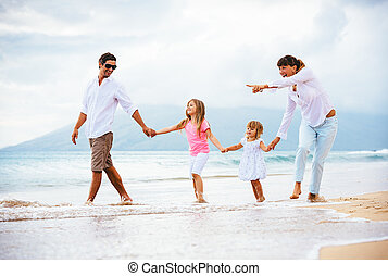 Happy young family walking on the beach at sunset. Happy...
