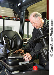 man with a laptop - A man working on forklift, filling in...