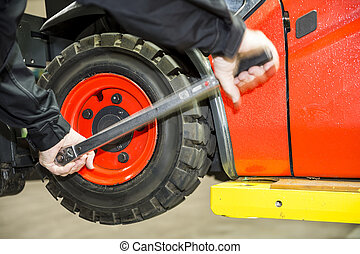 Chaning a forklift tyre - Maintenace on a forklift, a worker...
