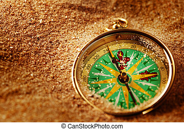 Compass on sand - Closeup of a compass laying on a sand