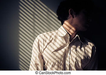 Man by window with shadows from blinds - Young man next to a...