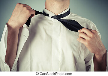 Young man tying a bow tie - Young man is showing how to tie...