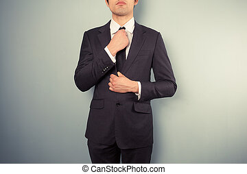 Young businessman adjusting his tie - A young businessman is...