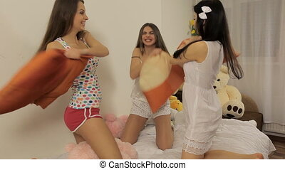 Three young women having fun (pillow fight)