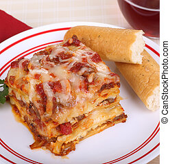 Lasagna Dinner - Portion of lasagna and bread sticks on a...