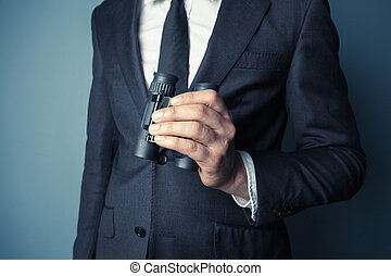 Businessman with binoculars - Businessman is holding...