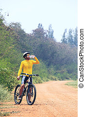 young bicycle cyclist man drinking fresh water from plastic...