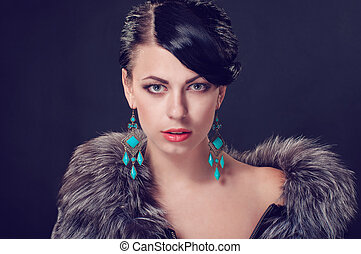 Young woman in a fur coat in beautiful earrings