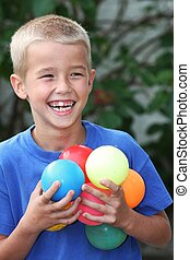 Young Lad and Balls - Happy laughing young boy playing with...