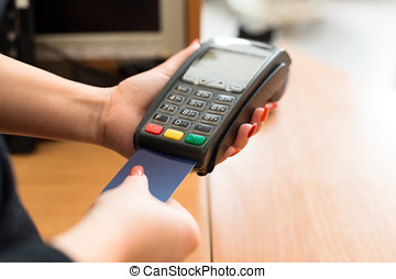 Woman pay by credit card in shop