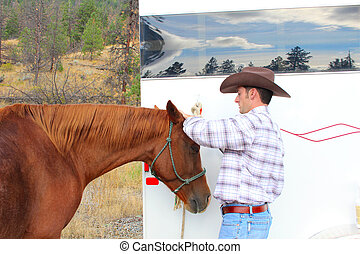 Horse grooming - Young cowboy grooming his horse at the...