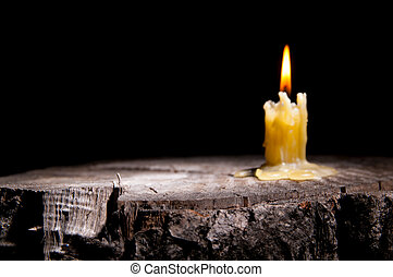 old candle on the black background - old candle stands on...
