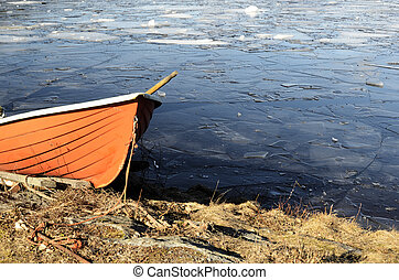 orange rescue boat on the shore of a frozen lake -...