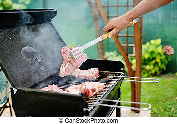 Man at a barbecue grill preparing meat for a garden party -...