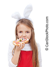 Little girl with bunny ears eating a sandwich