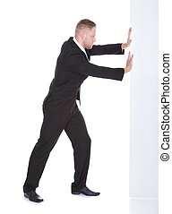 Businessman pushing the edge of a blank white sign leaning...