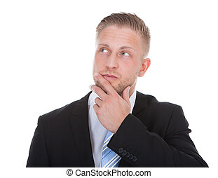 Businessman standing deep in thought with his hand to his...