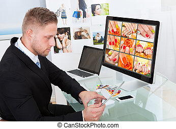 Businessman editing photographs - Businessman sitting at his...