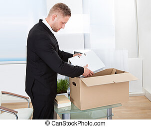 Businessman moving offices packing up all his personal...