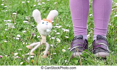 white rabbit marionette dancing on green grass