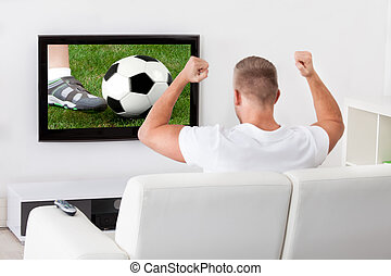 Excited soccer fan watching a game on television holding a...