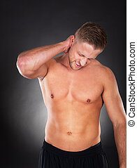 Fit muscular man massaging his neck in pain - Fit muscular...