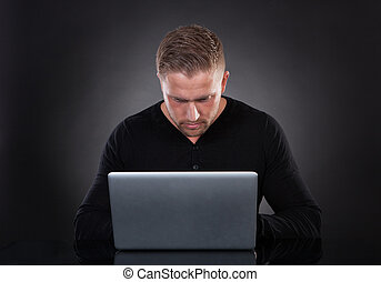 Man or hacker working on a laptop at night - Man or hacker...