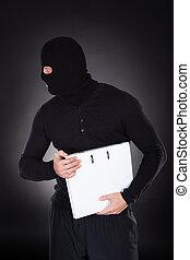 Thief in a balaclava stealing a file