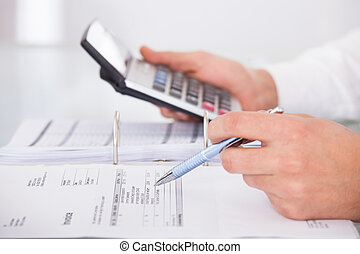 Businessman Using Calculator In Office - Cropped image of...