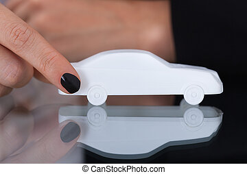 Businesswoman Holding Toy Car - Midsection of businesswoman...