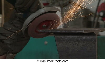 Man smoothing piece of metal - Worker smoothing piece of...