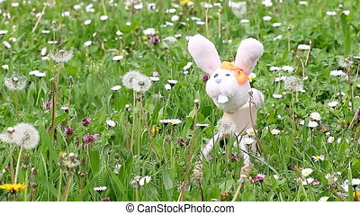 white rabbit marionette on green grass